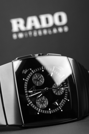 cronógrafo: San Petersburgo, Rusia - 18 de junio 2015: Rado Sintra Chrono, reloj cronógrafo para hombre hecha de cerámica de alta tecnología con cristal de zafiro sobre fondo oscuro con logotipo de la empresa. Enfoque selectivo Editorial