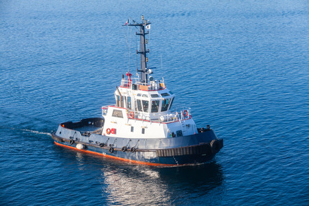 superstructure: Tug boat with white superstructure and dark blue hull underway on sea water Stock Photo