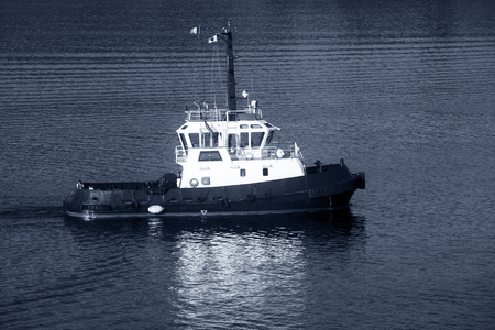 superstructure: Tug boat with white superstructure underway, side view, monochrome photo Stock Photo