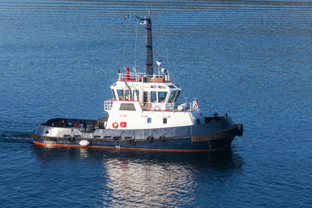 superstructure: Tug boat with white superstructure and dark blue hull underway, side view