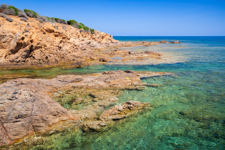 Coastal landscape with rocky wild beach and blue lagoon, Corsica island, France. Plage De Capo Di Feno
