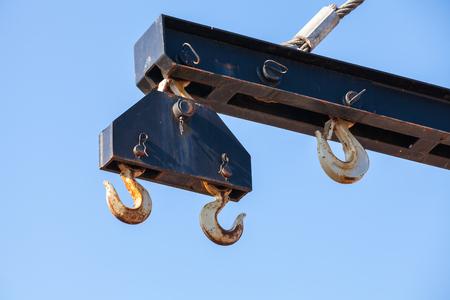 crane parts: Hooks hanging on beam of harbor crane over blue sky background