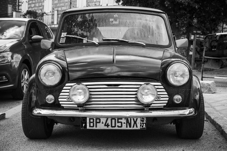 Quenza, France - July 1, 2015: Black Mini cooper car stands parked, closeup photo, front view Editorial