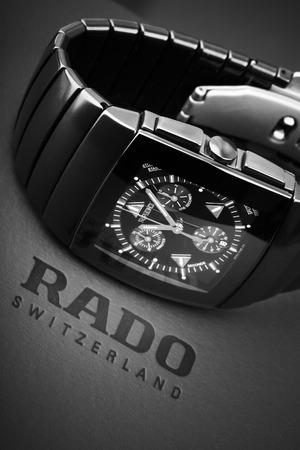 cronografo: San Petersburgo, Rusia - 18 de junio 2015: Rado Sintra Chrono, reloj cronógrafo para hombre hecha de cerámica de alta tecnología con cristal de zafiro sobre fondo gris oscuro con logotipo de la empresa. Enfoque selectivo