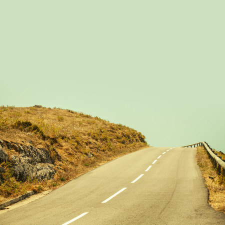 tonal: Empty mountain asphalt road and clear blue sky, square composition, vintage tonal correction filter, old style effect