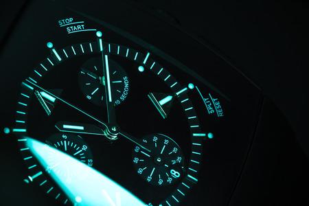 cronógrafo: Hombre de lujo del reloj del cronógrafo, trato de reloj con iluminación verde azul. Primer estudio en tonos azul foto con enfoque selectivo Foto de archivo