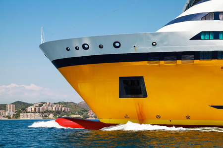 ship bow: Big yellow passenger ferry ship goes on speed in the Mediterranean Sea. Bow fragment