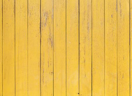 amarillo: Vieja pared de madera de color amarillo con una capa de pintura agrietada, foto de fondo detallada textura