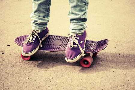 skateboard shoes: Teenager feet in jeans and gumshoes on a skateboard, photo with warm retro tonal correction,  old style