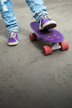 skateboard shoes: Feet in a blue jeans and gumshoes and skateboard, selective focus with shallow DOF Stock Photo