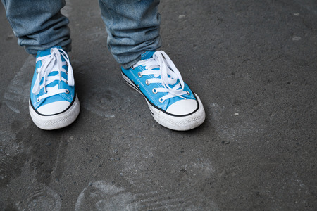 tearing down: Blue sneakers in teenager feet stand on dark gray asphalt. Closeup photo with selective focus