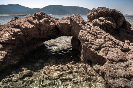 Natural stone grotto on the Mediterranean coast, South Corsica, France. Plage De Capo Di Feno. Dark tonal correction filter effect Banco de Imagens
