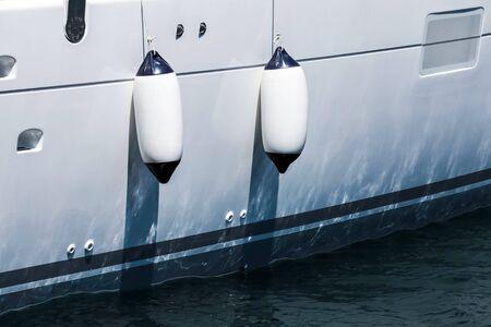 pleasure ship: Small ship fenders hanging above luxury white pleasure yacht hull