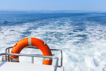 despertar: Colgante Lifebuoy rojo en los pasamanos de popa del bote de rescate rápido de seguridad