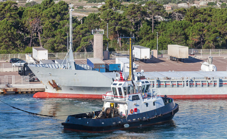 superstructure: Small tug boat with white superstructure and dark blue hull works in port