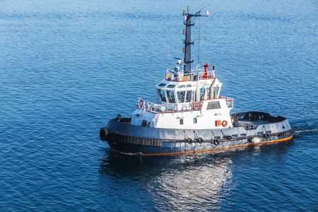 superstructure: Small tug boat with white superstructure and dark blue hull underway on sea water