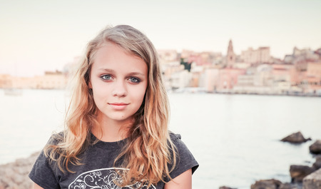 Outdoor portrait of blond Caucasian teenage girl standing on a seacoast, Gaeta, Italy