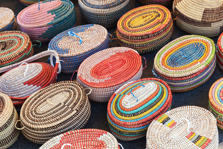 Colorful African wicker baskets stand on a counter in marketplace
