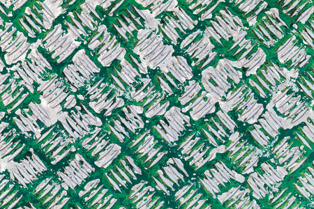 diamond plate: Grungy metal surface with diamond plate pattern under old green paint layer