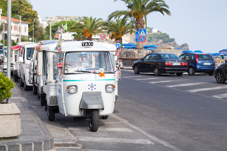roadside stand: Casamicciola Terme, Italy - August 12, 2015: Micro taxi stand parked on a roadside, white Ape Car is a three-wheeled light commercial vehicle produced since 1948 by Piaggio Editorial