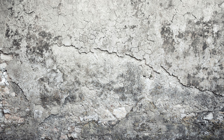 Old weathered concrete wall with damages and cracks on gray stucco, background texture