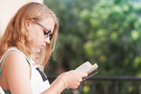 Blond Caucasian teenage girl sits on the balcony and read a book