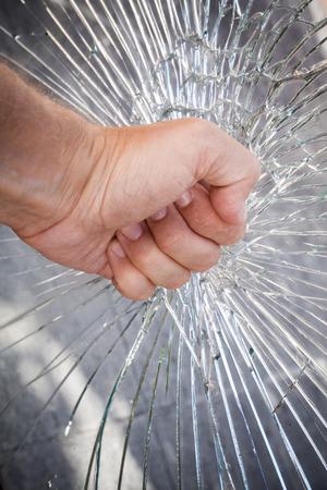 glass break: Strong male fist with broken window glass Stock Photo