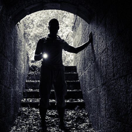 enters: Young man with a flashlight enters the stone tunnel and looks in the dark, square photo Stock Photo