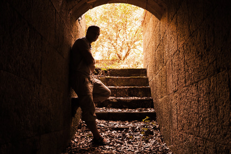 tonal: Young man stands in dark stone tunnel with glowing end, warm tonal correction filter
