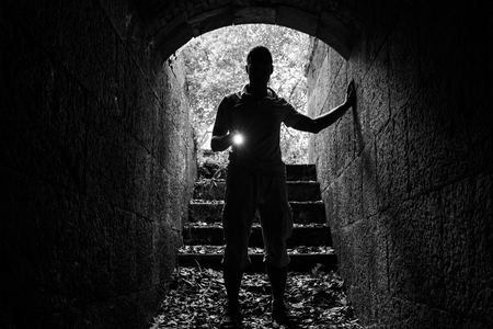 scary man: Young man with a flashlight enters the stone tunnel and looks in the dark, monochrome photo