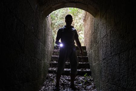 enters: Young man with a flashlight enters stone tunnel and looks in the dark