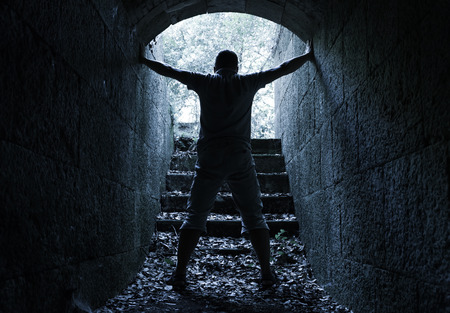 correction: Young man stands in dark stone tunnel with glowing end, blue tonal correction filter