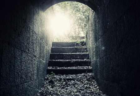 Glowing exit with stairs and lens flare from dark abandoned concrete tunnel interior, tonal correction filter Stock Photo