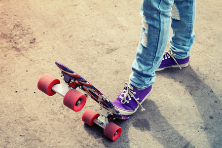 tonal: Teenager feet in blue jeans and gumshoes on a skateboard, photo with warm retro tonal correction, old style