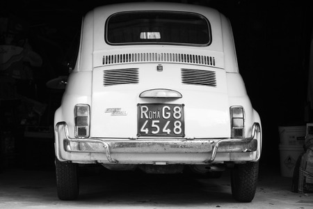 Casamicciola Terme, Italy - August 12, 2015: Old white fiat 500 L car stands in dark garage, rear view Editorial