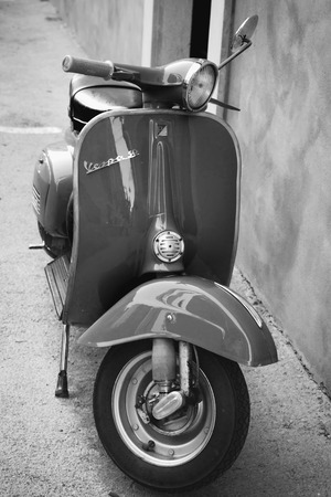 Gaeta, Italy - August 19, 2015: Classic Vespa scooter stands parked near the wall, vertical photo Editorial