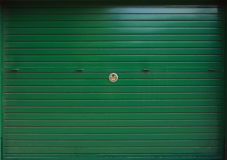 security shutters: Closed green metal garage gate, background texture
