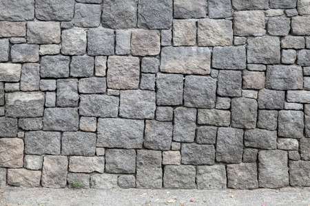 Gray stone wall and asphalt road, background texture Standard-Bild