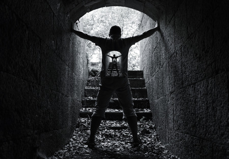 brain mysteries: Infinity inner world concept, young man stands in dark stone tunnel with glowing end