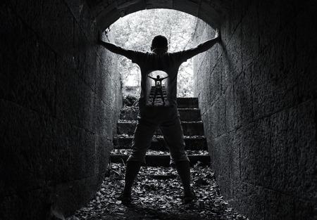 Infinity innerlijke wereld concept, jonge man staat in een donkere steen tunnel met gloeiende einde Stockfoto