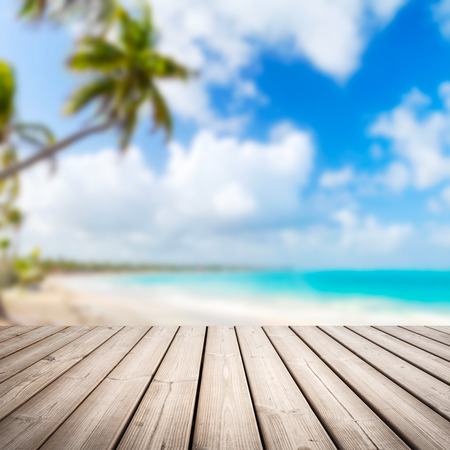 sunny beach: Empty wooden pier background over blurred tropical beach coastal landscape with palm tree, cloudy sky and bright sea water Stock Photo