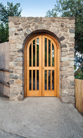stone arch: Yellow wooden door in stone arch, front view Stock Photo