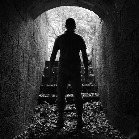 Young man stands in dark stone tunnel with glowing end, black and white square photo