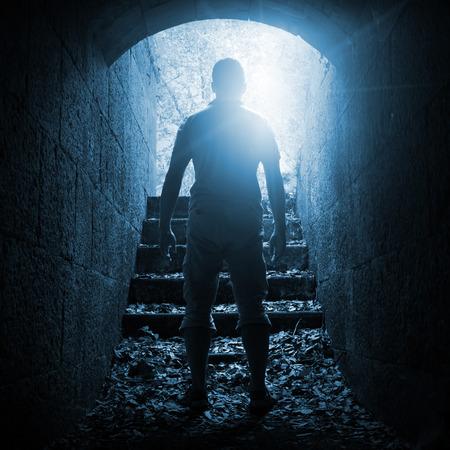 tunel: Hombre joven se coloca en el túnel de piedra oscura con final brillante, tonos azules foto cuadrada