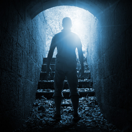 standing stone: Young man stands in dark stone tunnel with glowing end, blue toned square photo