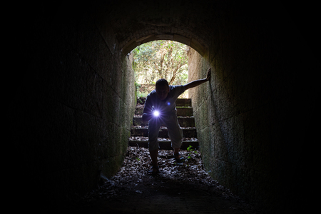 young fear: Young man with a flashlight enters the stone tunnel and looks inside with attention and fear