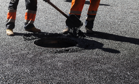 asphalting: Urban road under construction, asphalting in progress, workers with a shovel near sewer manhole, feet fragment Stock Photo