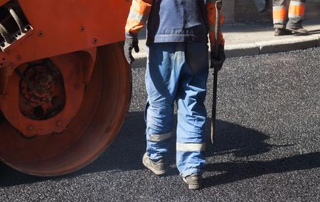 asphalting: Urban road under construction, asphalting in progress, worker with a shovel near orange  roller