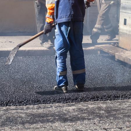 asphalting: Urban road under construction, asphalting in progress, worker with a shovel in blue uniform