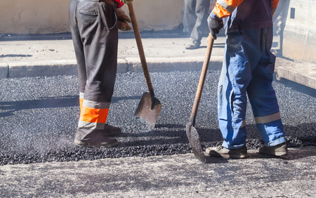 asphalting: Urban road under construction, asphalting in progress, workers with shovels